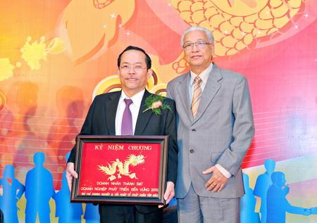 Bác sĩ Bùi Cúc (trái) nhận kỉ niệm chương Doanh nhân thành đạt – Doanh nghiệp phát triển bền vững và Tiến sĩ Cao Sĩ Kiêm (phải)
